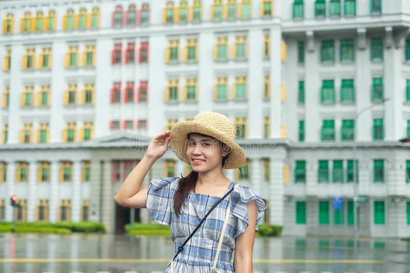 Young Woman traveling with hat, happy Asian traveler visit at rainbow colorful building in Clarke Quay, Singapore. landmark and royalty free stock images