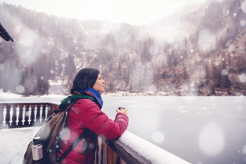 A young woman traveling in the mountains in winter, drinking hot tea against the backdrop of a frozen lake, the Alps royalty free stock images