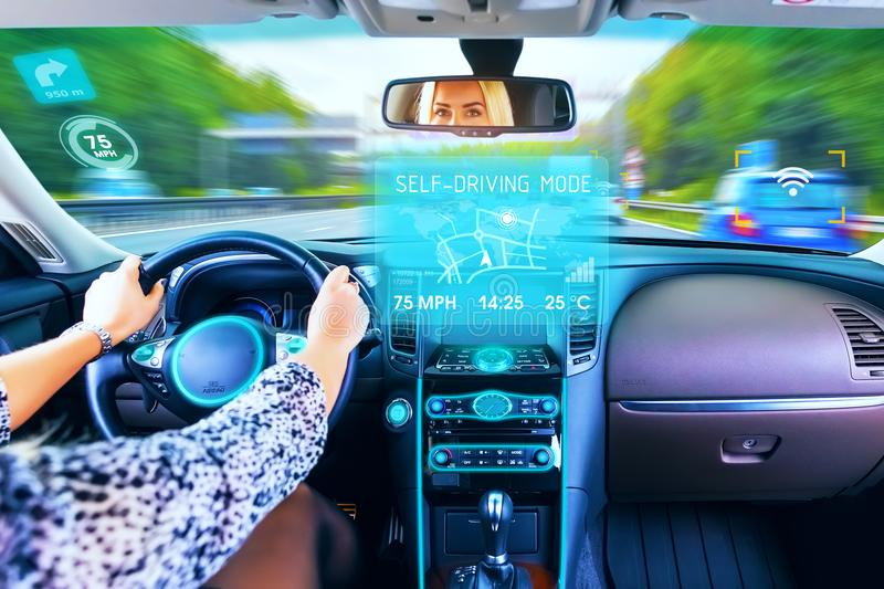 Young woman traveling in self driving car. Young woman traveling in self driving mode autopilot business luxury car or auto on the highway or autobahn with stock image