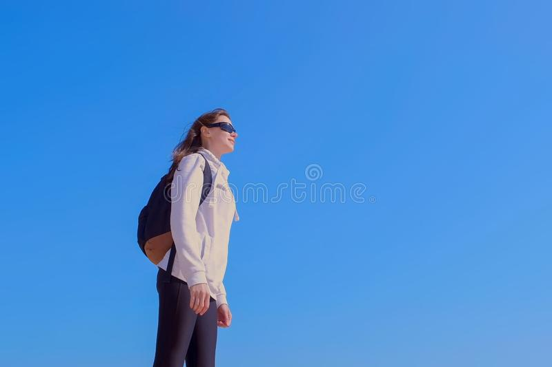Woman traveller with backpack enjoys nature on blue sky background on vacation. Young woman traveller with backpack in sunglasses is enjoying nature on blue sky royalty free stock images