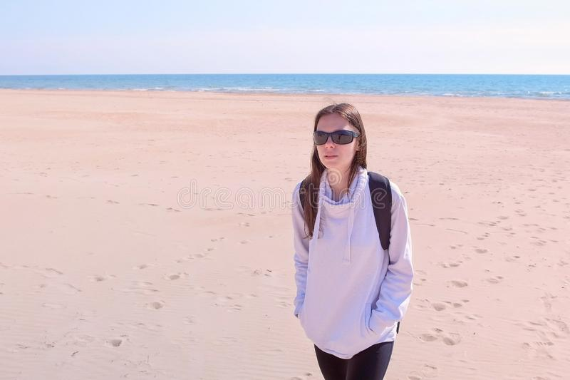 Woman tourist walks on sea sand beach off-season travel outdoors activities. Young woman traveller in sportswear and sunglasses with backpack. She is walking at stock image