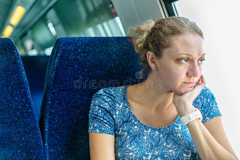 Sad woman at the window of a train royalty free stock images