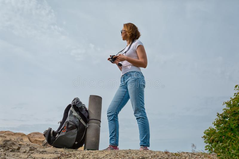 A young woman travels with a backpack and decided to take some photos in a beautiful place.  royalty free stock images
