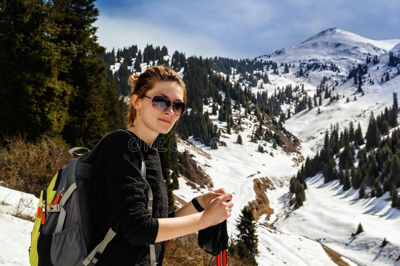 Young woman with trekking sticks in mountainsYoung woman with trekking sticks royalty free stock photos