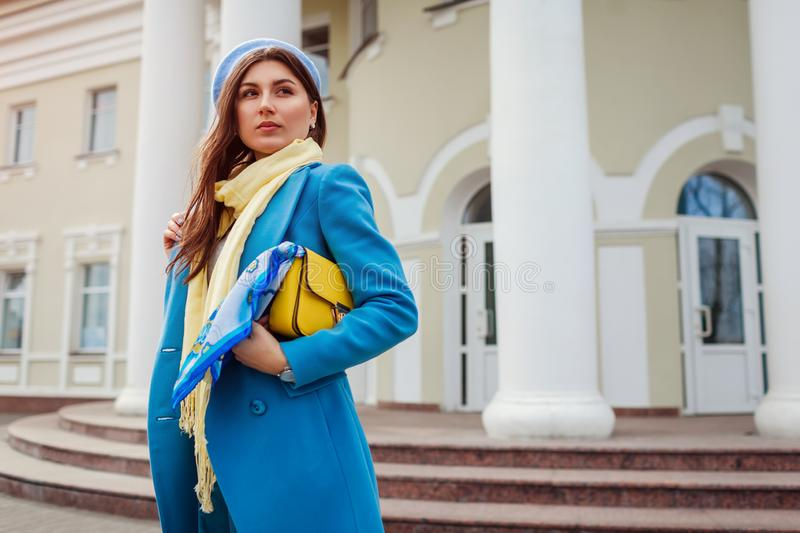 Young woman in trendy blue coat walking in city holding stylish handbag. Spring female clothes and accessories. Fashion royalty free stock photos