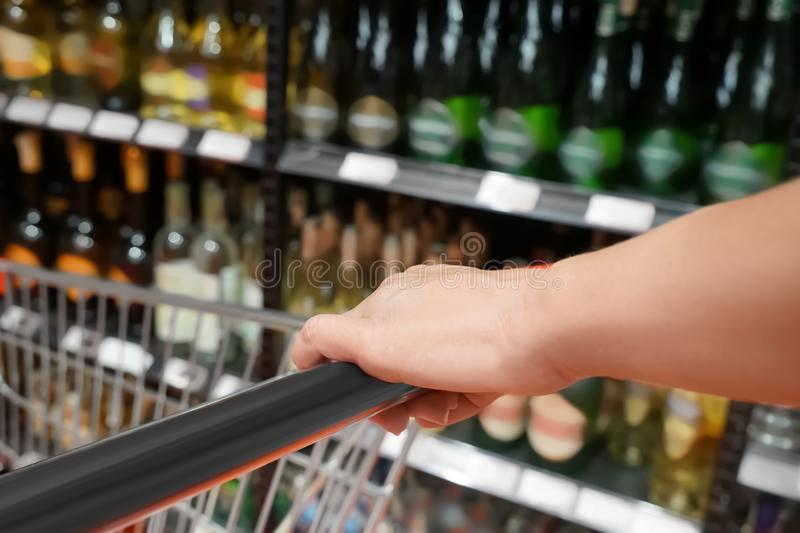 Young woman with trolley choosing products royalty free stock photo