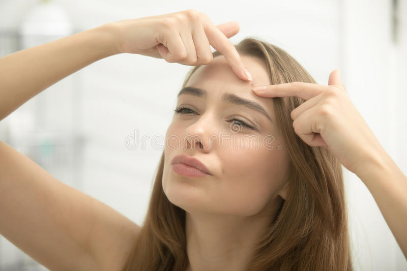 Young woman troubled checking wrinkles on her forehead. Young woman troubled checking acnes on her forehead, looking at the bathroom mirror. Beauty, skin care royalty free stock images
