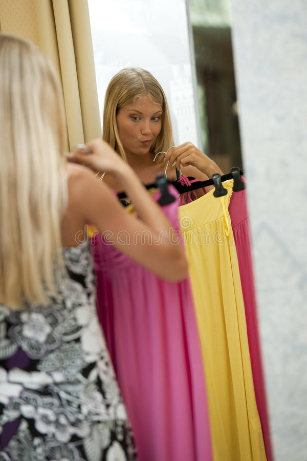 Young woman trying dress on. Trying to decide stock photos