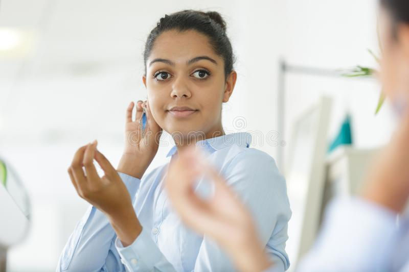 Young woman trying on earrings looking in mirror stock photo