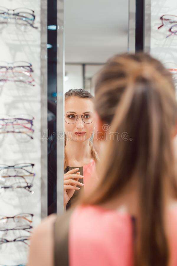 Young woman trying fashionable glasses in optometrist store royalty free stock photos