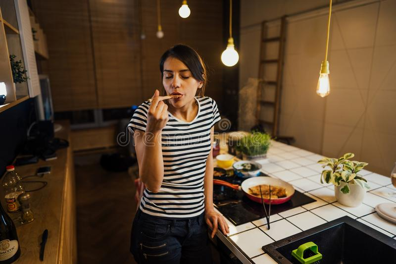 Young woman trying out healthy meal in home kitchen.Making dinner on kitchen island standing by induction hob.Preparing fresh. Vegetables,enjoying spice aromas royalty free stock images