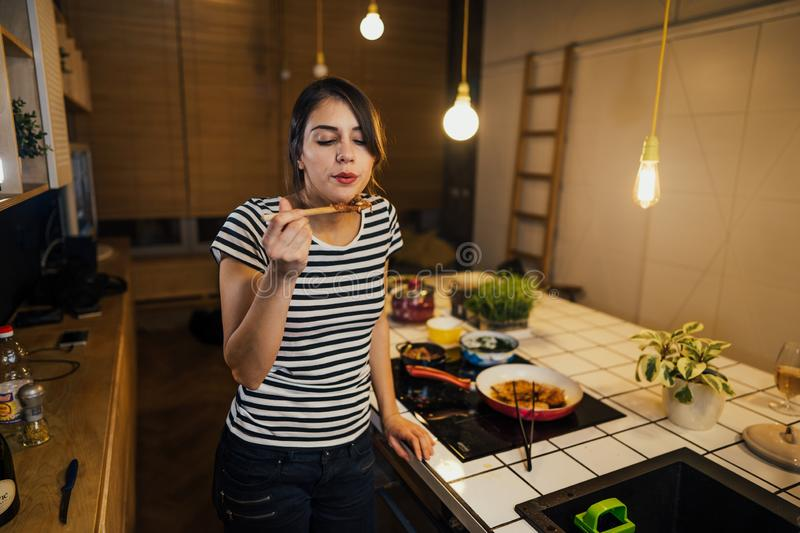 Young woman trying out healthy meal in home kitchen.Making dinner on kitchen island standing by induction hob.Preparing fresh. Vegetables,enjoying spice aromas stock image