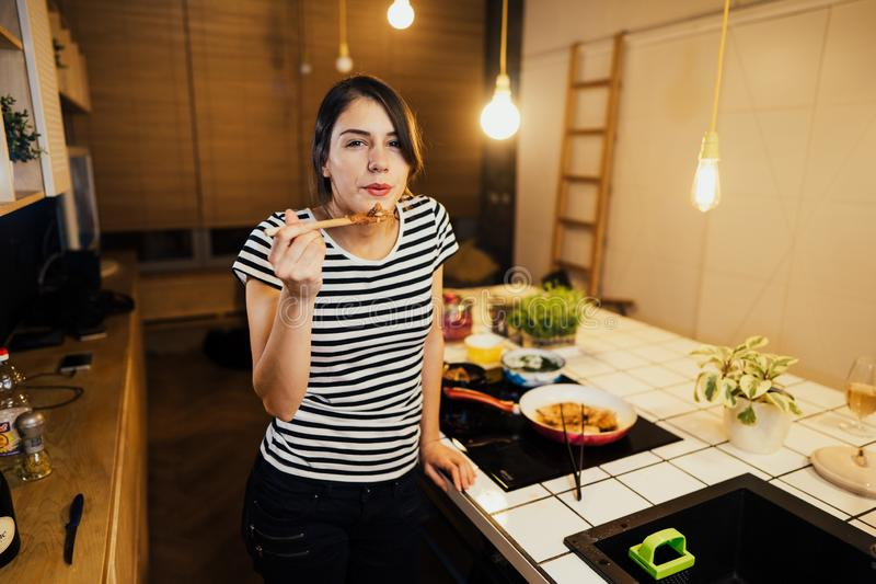 Young woman trying out healthy meal in home kitchen.Making dinner on kitchen island standing by induction hob.Preparing fresh. Vegetables,enjoying spice aromas royalty free stock photos