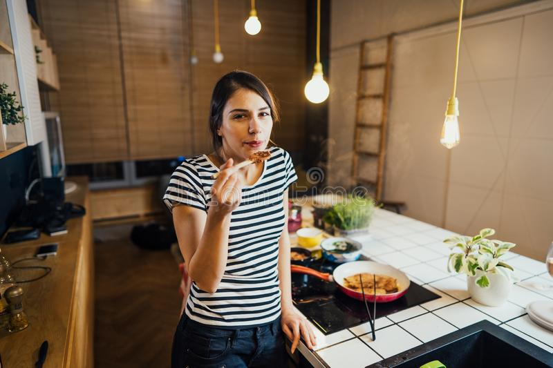 Young woman trying out healthy meal in home kitchen.Making dinner on kitchen island standing by induction hob.Preparing fresh. Vegetables,enjoying spice aromas royalty free stock photo