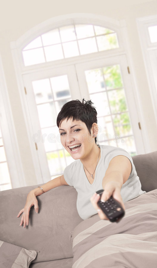 Young woman with TV remote stock photography
