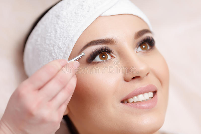 Young woman tweezing her eyebrows in beauty saloon stock photos