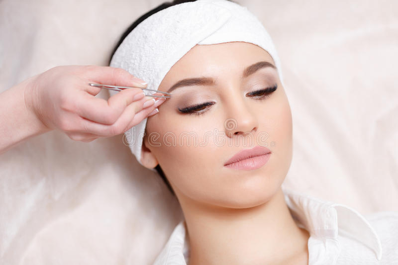 Young woman tweezing her eyebrows in beauty saloon. Beautiful young woman gets eyebrow correction procedure. Young woman tweezing her eyebrows in beauty saloon royalty free stock photo