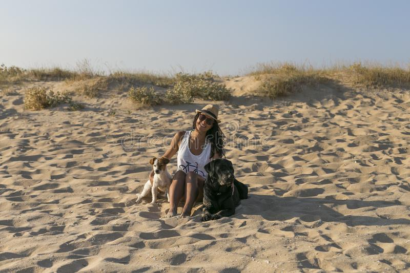 Young woman with two dogs at the beach. Summer time royalty free stock photo