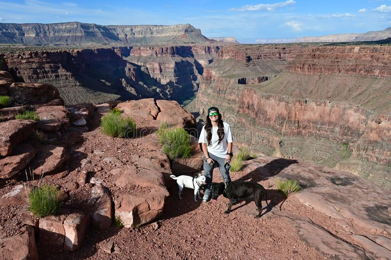 Young woman with two dogs at Toroweap Overlook in the Grand Canyon. Young woman with her two dogs at Toroweap Overlook in Grand Canyon National Park, Arizona royalty free stock image