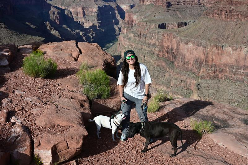 Young woman with two dogs at Toroweap Overlook in the Grand Canyon. Young woman with her two dogs at Toroweap Overlook in Grand Canyon National Park, Arizona stock photos
