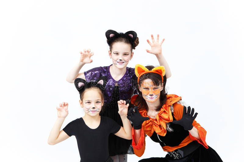 Young woman and two girls in cat carnival costumes posing stock photography