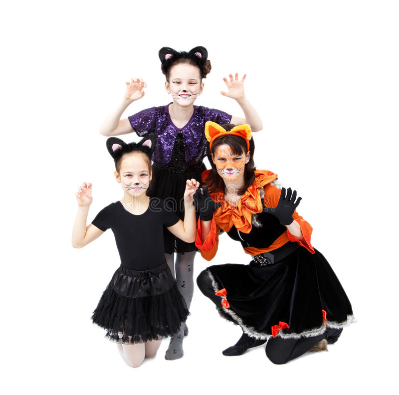Young woman and two girls in cat carnival costumes posing royalty free stock image