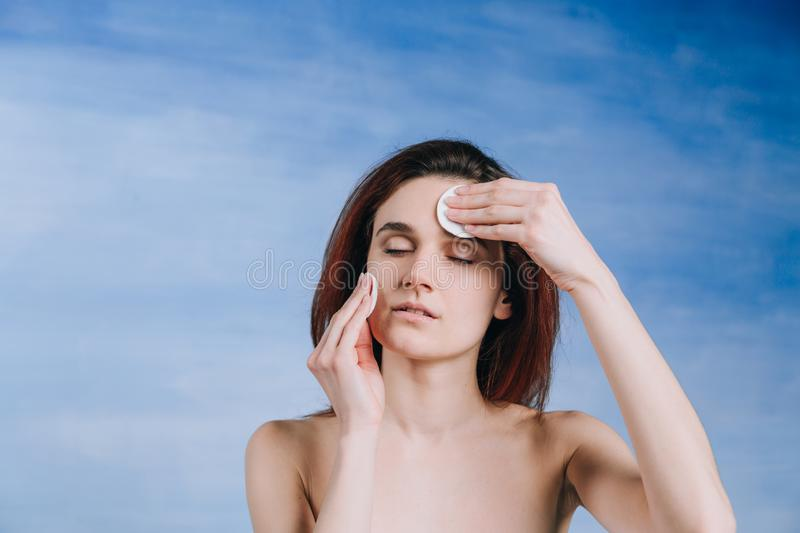 Young woman with a two sponge wihte background cotton pads cleans problem skin with closed eyes royalty free stock image