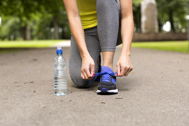 Young woman tying laces of running shoes before training. Healthy lifestyle concept stock image