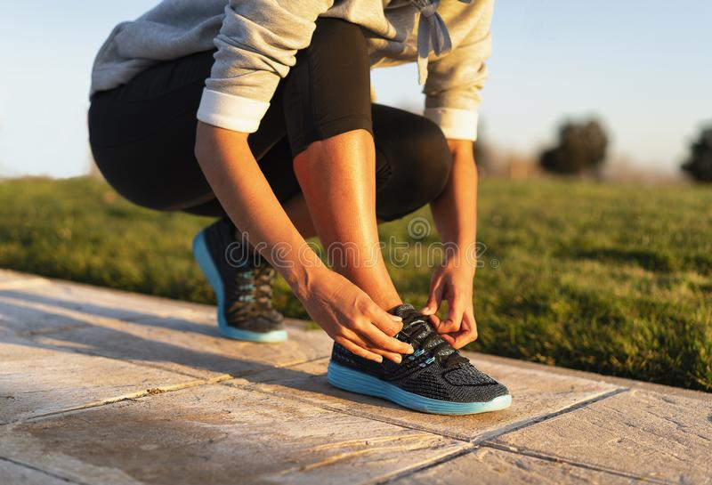 Young woman tying shoelace of sneakers to make outwork training running. Fitness and healthy lifestyle royalty free stock photography