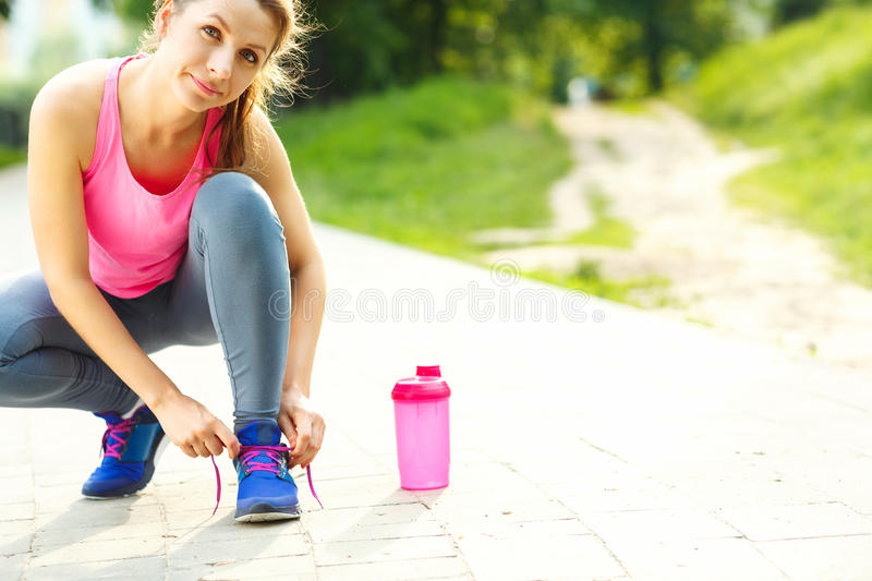 Young woman tying shoelaces before running stock photo
