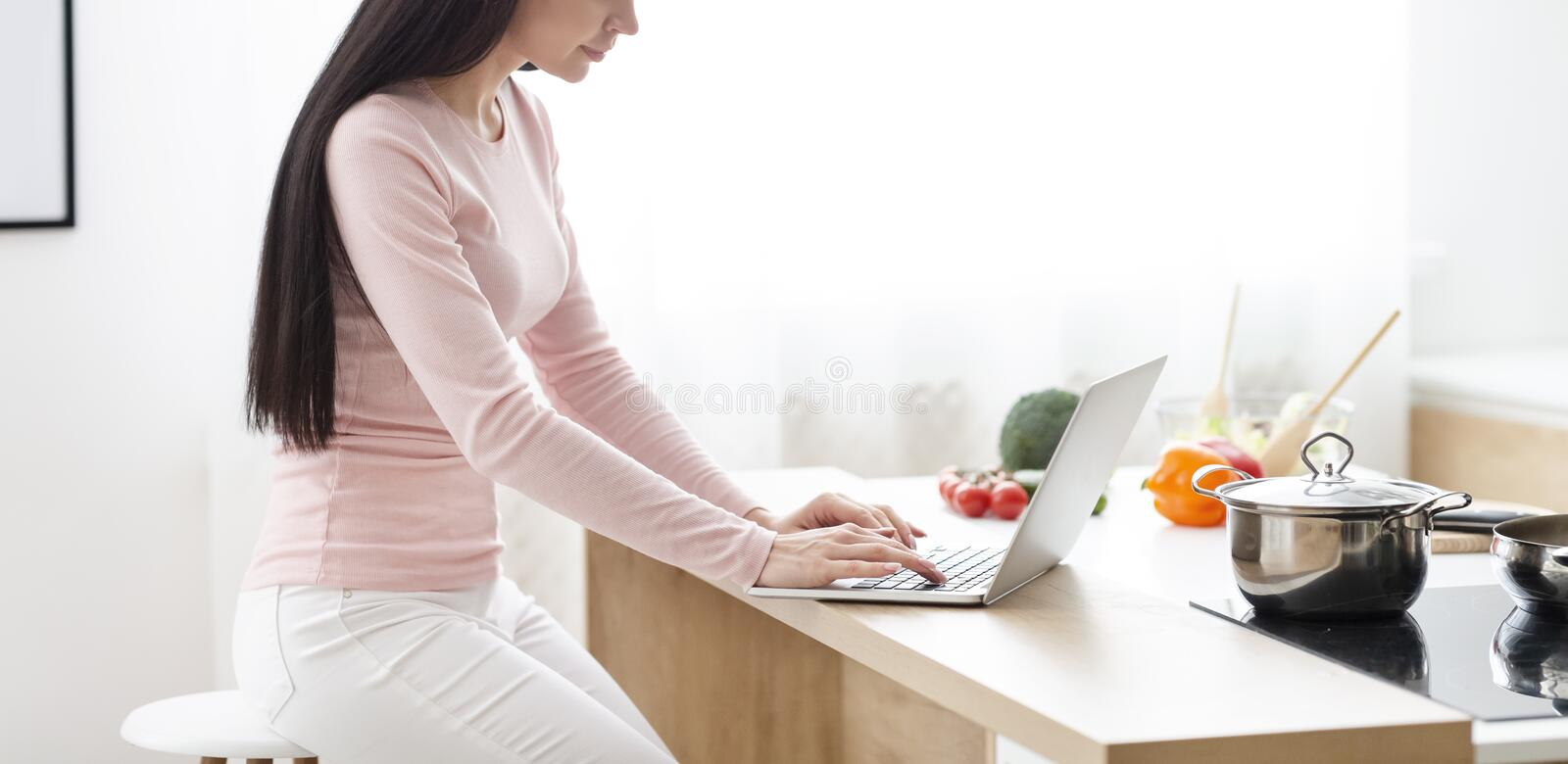 Young woman typing on laptop, sitting at kitchen stock photos