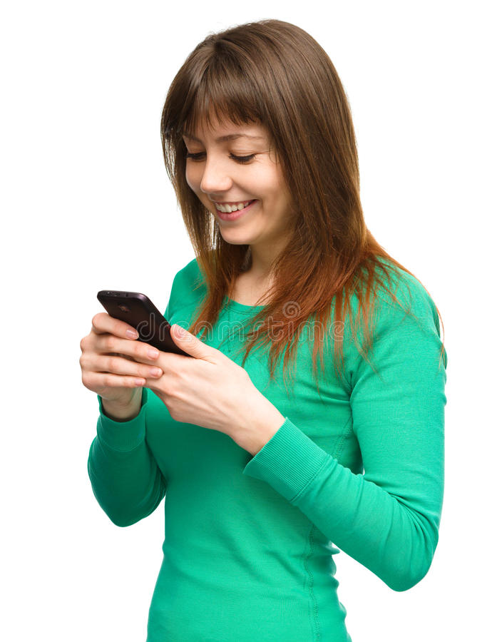 Young woman is typing sms message on her phone. Young cheerful woman is typing sms message on her phone, isolated over white stock photos