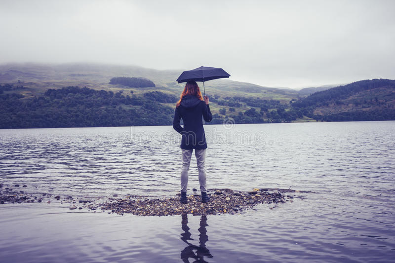 Young woman with an umbrella standing in lake stock image