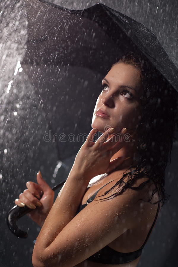 Young woman with umbrella under the rain royalty free stock photo