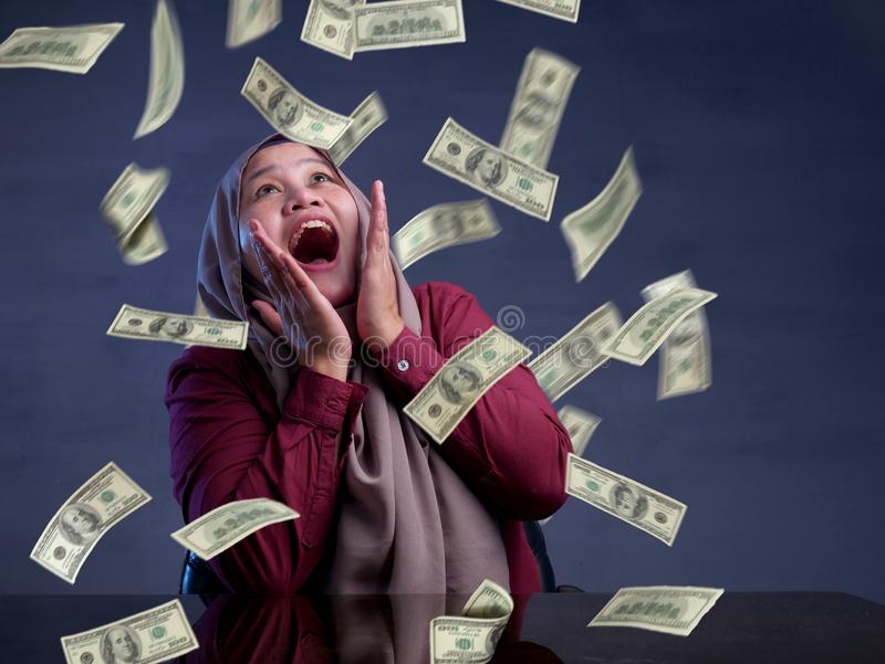 Young Woman Under Rain of Money. Portrait of happy successful young Asian billionaire muslim woman smiling happily under rain of money. Wealth investment stock photo