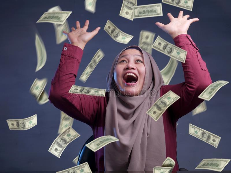 Young Woman Under Rain of Money. Portrait of happy successful young Asian billionaire muslim woman smiling happily under rain of money. Wealth investment royalty free stock images