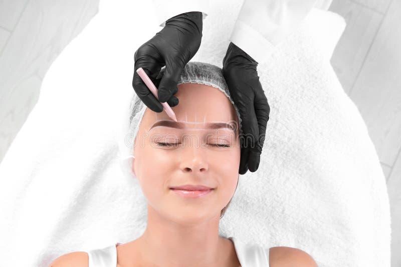 Woman undergoing eyebrow correction procedure in salon, top view. Young woman undergoing eyebrow correction procedure in salon, top view royalty free stock photos