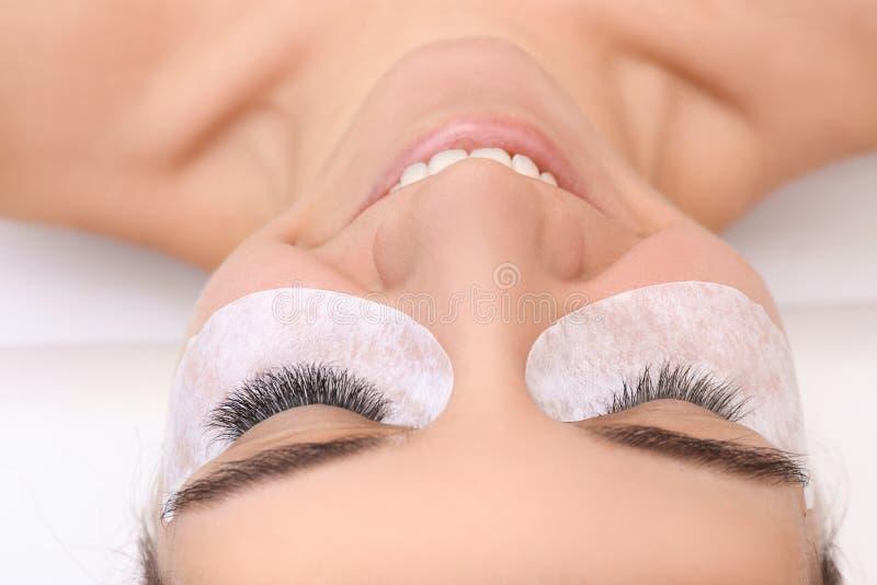Young woman undergoing eyelash extension procedure. Closeup stock photos