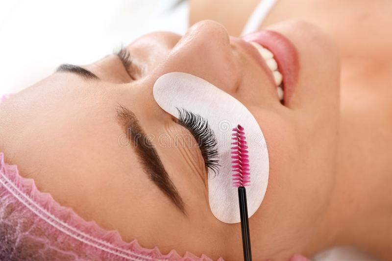 Woman undergoing eyelash extensions procedure, closeup. Young woman undergoing eyelash extensions procedure, closeup stock photography