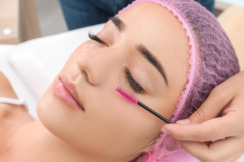 Woman undergoing eyelash extensions procedure, closeup. Young woman undergoing eyelash extensions procedure, closeup stock images