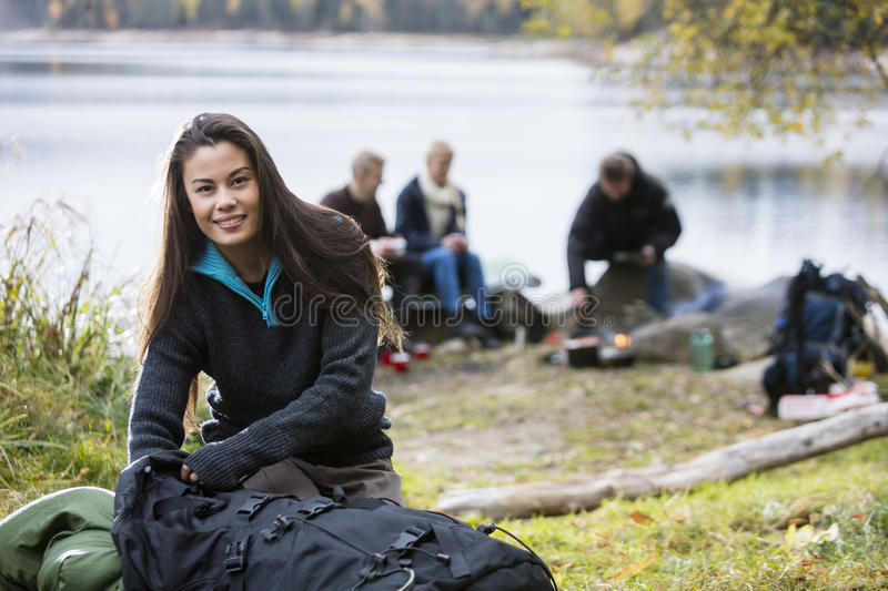 Young Woman Unpacking Backpack At Campsite stock photos