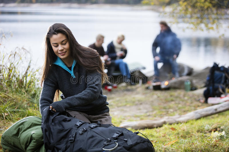 Young Woman Unpacking Backpack At Campsite stock photo
