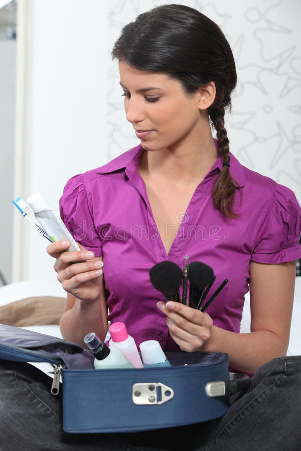 Young Woman Unpacking Her Luggage Royalty Free Stock Image