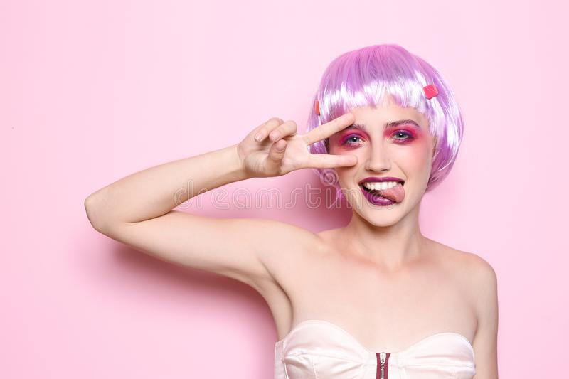 Young woman with unusual hair and professional makeup showing victory gesture on color background royalty free stock photos