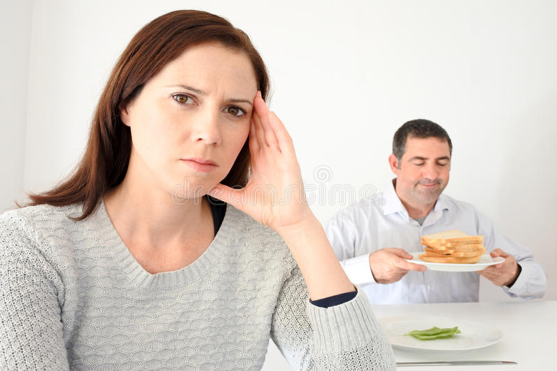Young woman upset when her partner eat and enjoys carbohydrates stock images