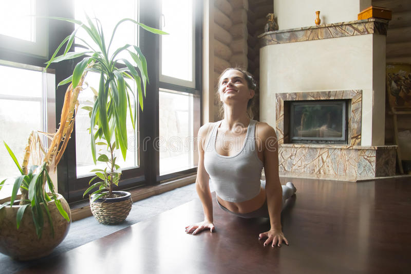 Young woman in upward facing dog pose, home interior background. Young attractive smiling woman practicing yoga, fitness, stretching in upward facing dog stock photography