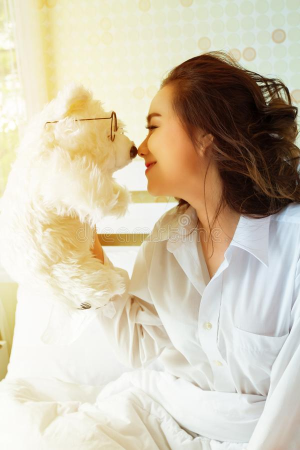 Young beautiful woman and white teddy bear in bedroom royalty free stock images