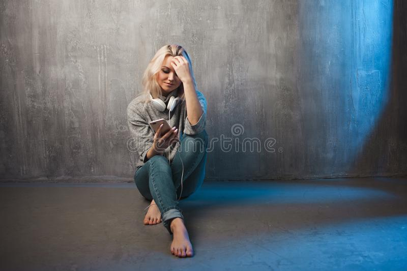 Young woman uses a smartphone. listening to a podcast or music, mobile applications stock photography
