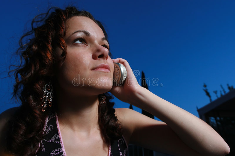 Young woman using cell phone. Young woman calling on a cell phone at night royalty free stock photo