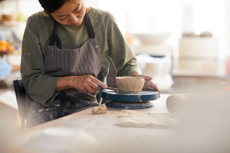 Young woman using cutter while making bowl. Serious concentrated young Asian woman in apron sitting at table and using cutter while making bowl in workshop stock photography